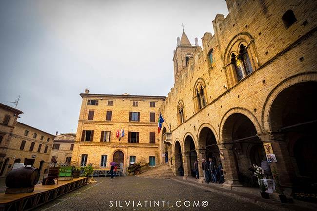 Montecassiano - Piazza Unita d'Italia con Palazzo Compagnucci di fronte ed a sinistra il Palazzo dei Priori. Alle spalle la Chiesa di San Marco